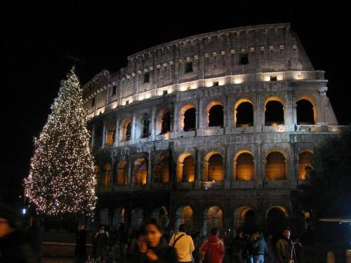 Italy - Colosseum lit up at night with people milling about at its base