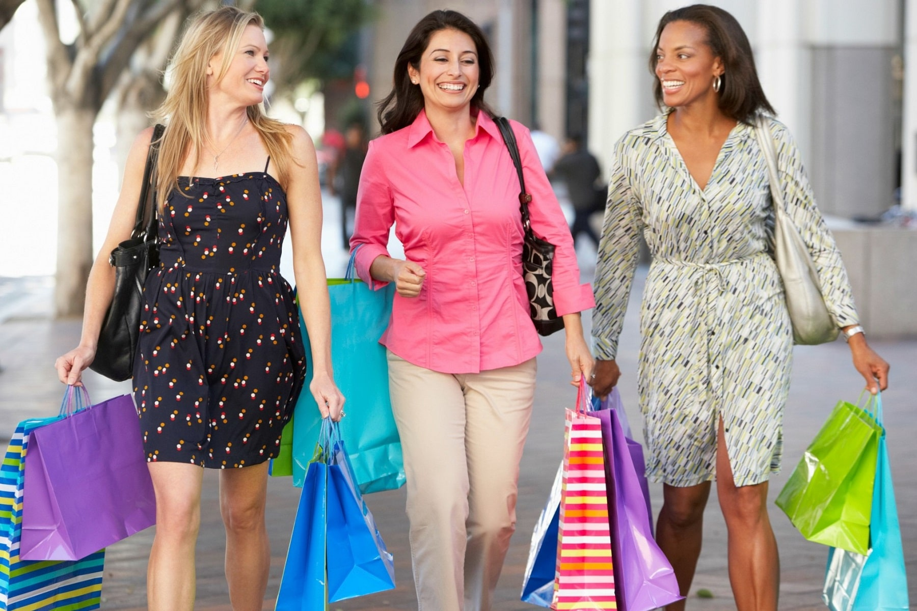 Three women holding shopping bags in Midtown Atlanta