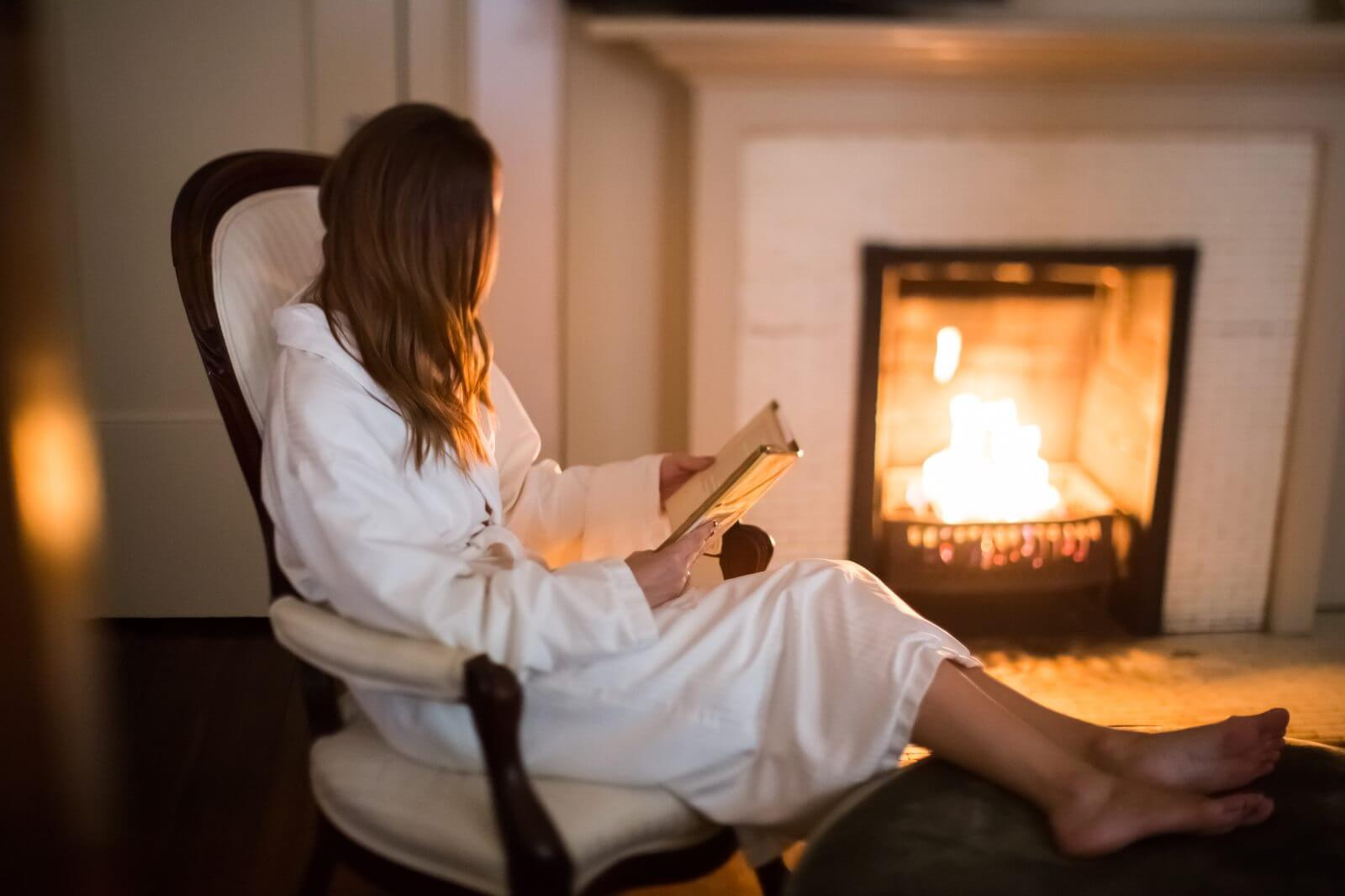 Woman reading by the fire in Hinman