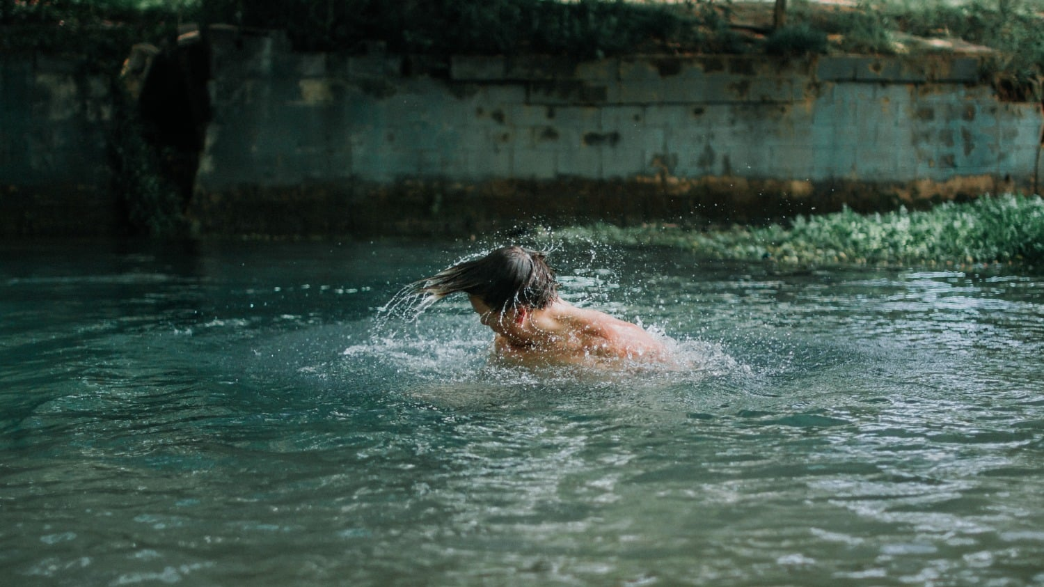 caucasian man in swimming hole shaking water off his head