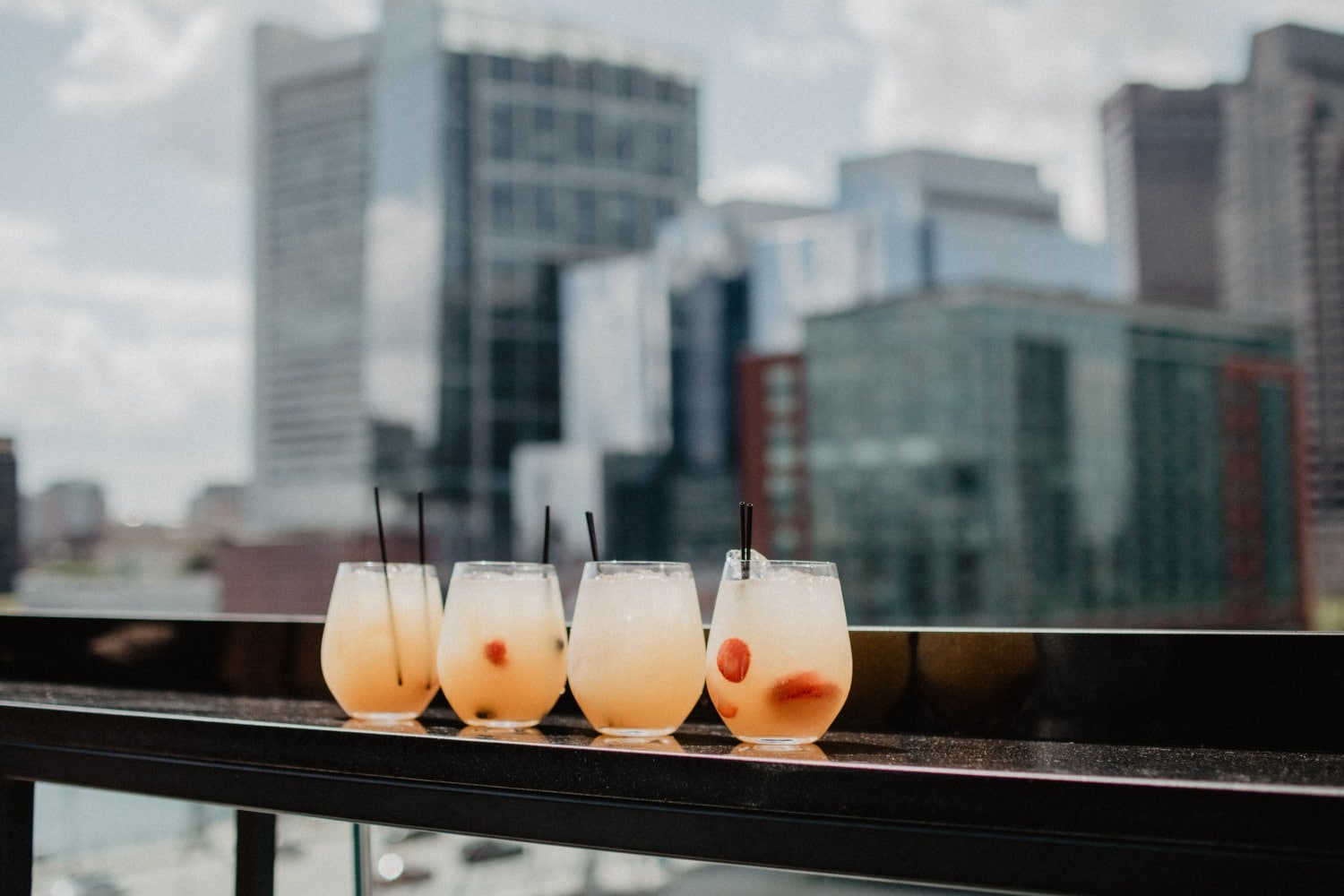 4 cocktails on rooftop bar with skyline in background