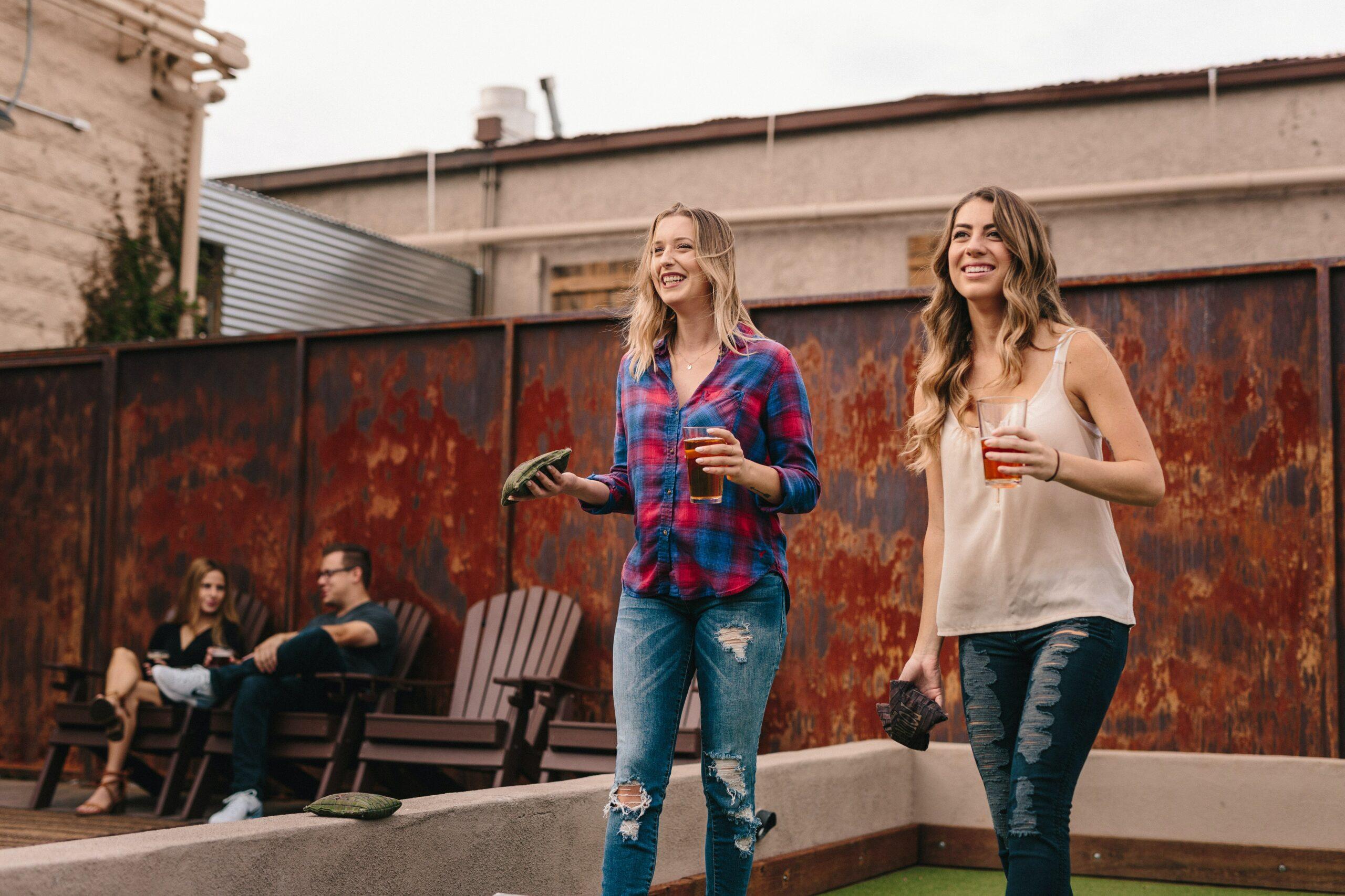 two white women playing cornhole on rooftop bar