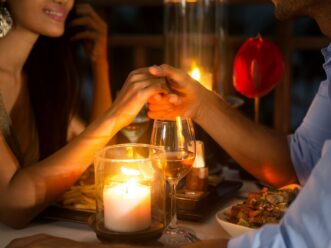 A man and woman holding hands during dinner at The Lawrence in Midtown Atlanta