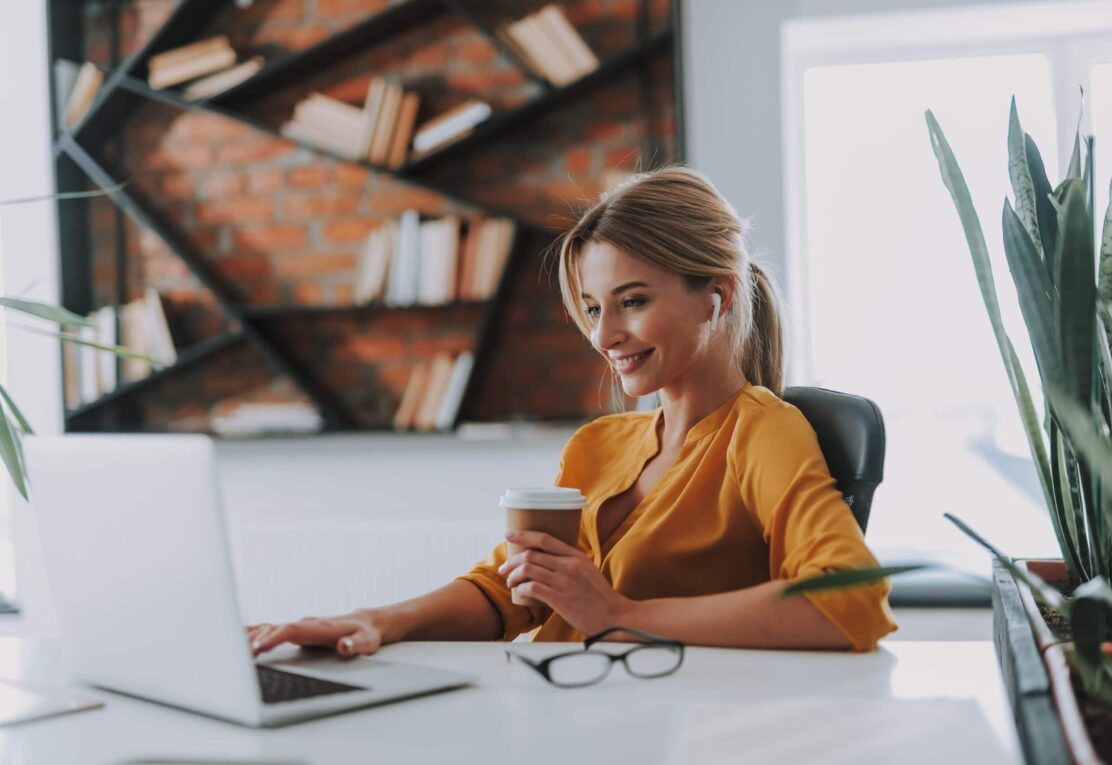 white woman in yellow shirt smiling at laptop holding coffee