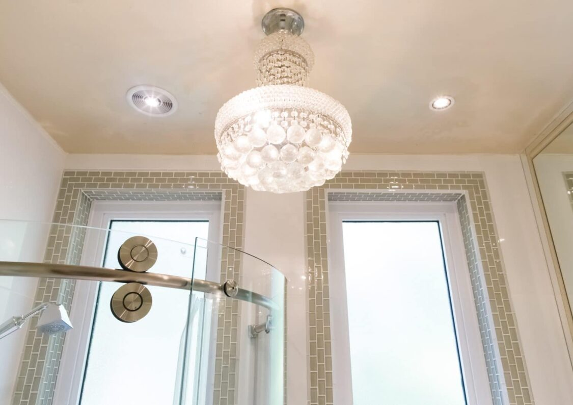 white luxe chandelier in bright white bathroom with green tile surrounding two rectangular windows and top of glass curved shower