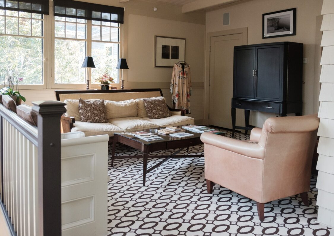 sleek sun room with leather chair, bold patterned flooring, and brown and beige tones