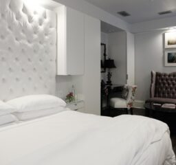 Stedman Suite bed and velvet sofa to the side with four colored portraits above in Stonehurst Place