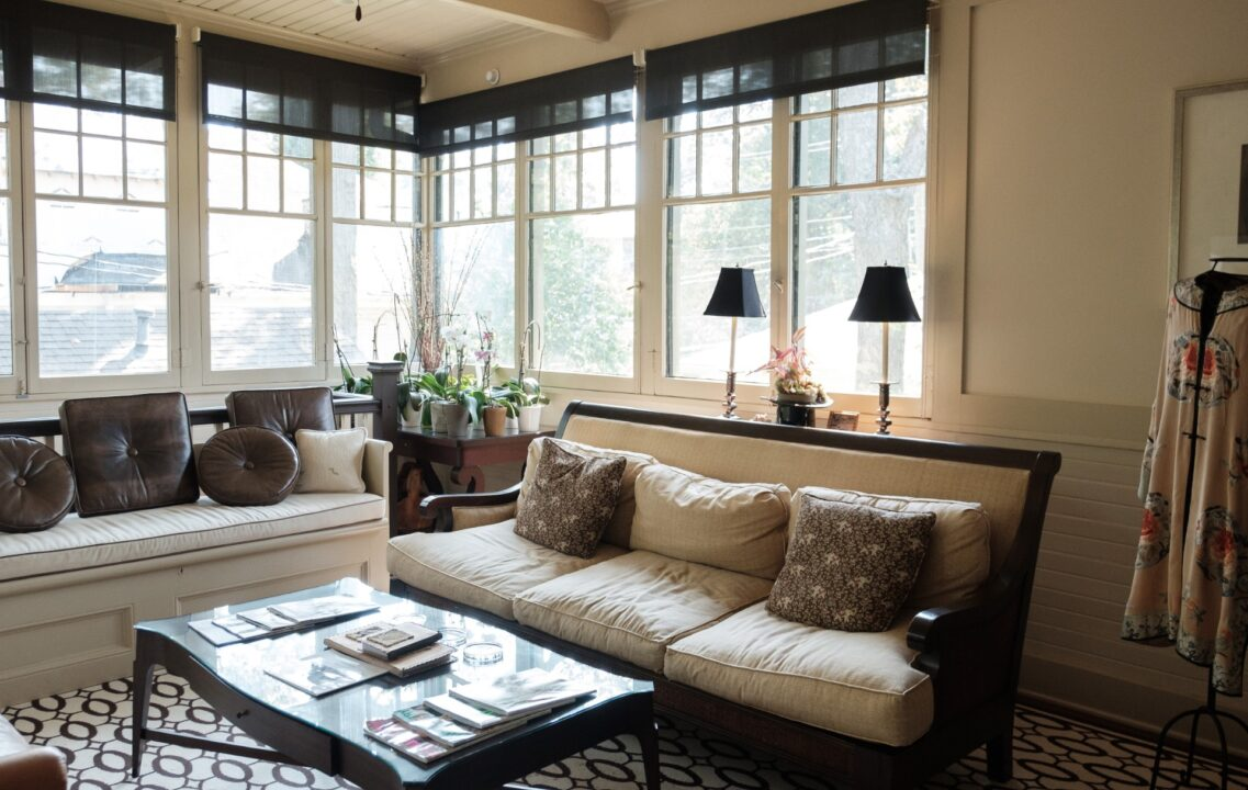 sleek sun room with white couch, bold patterned flooring, and brown and beige tones large windows