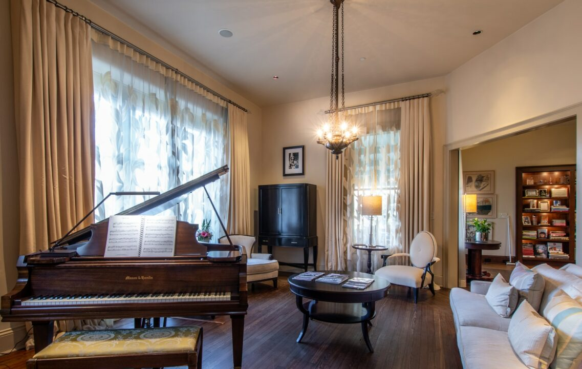 Piano room with sitting area and a round wood coffee table with magazines on top