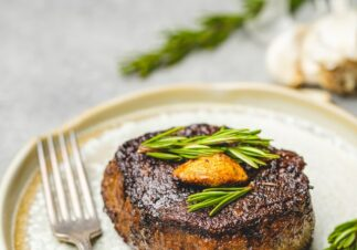 cooked juicy steak with rosemary and garlic garnish on neutral ceramic plate and silver fork