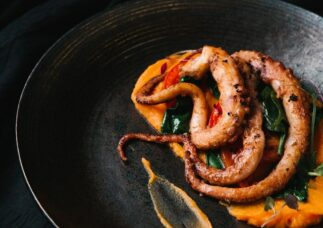 octopus cooked on black plate with orange mash