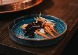 carrots and dark food on bright blue ceramic plate bowl in moody wooden setting