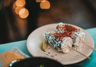two elote corn cobs on sticks with lime wedge on cream colored plate on blue surface