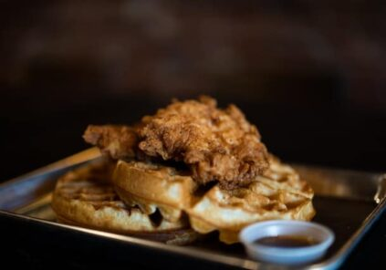 chicken and waffles on dark plate with dark background and syrup cup in foreground
