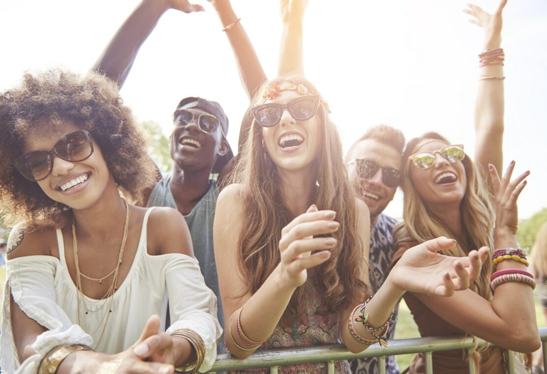 young adults wearing sunglasses in summer clothes outside smiling at concert