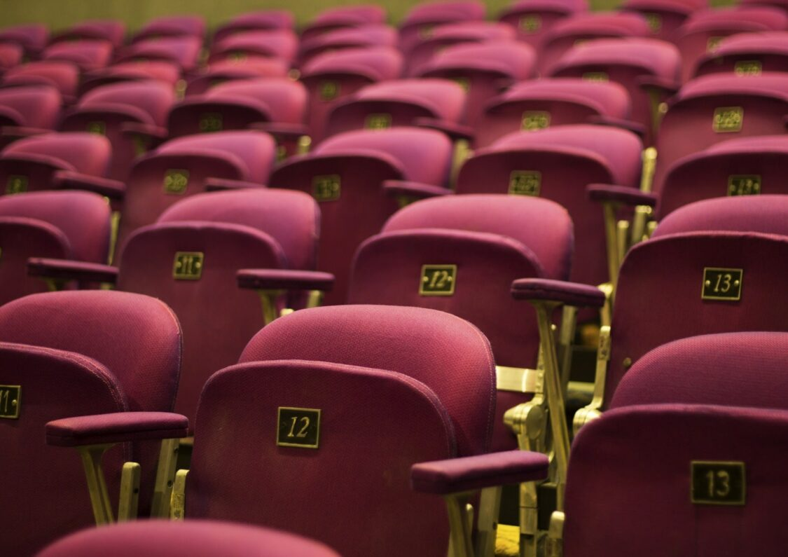 red theater seats with gold numbers and gold accents