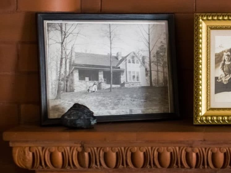three black and white photos in frames on wood mantle
