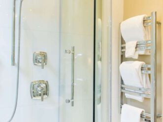 White towels on rack with glass sleek shower in bathroom at Stonehurst Place Guest Room Towel Warmer
