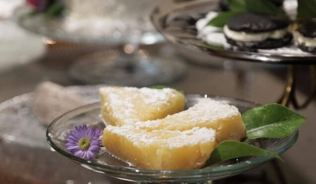 yellow dessert pie with powdered sugar on glass cake plate with other desserts in background