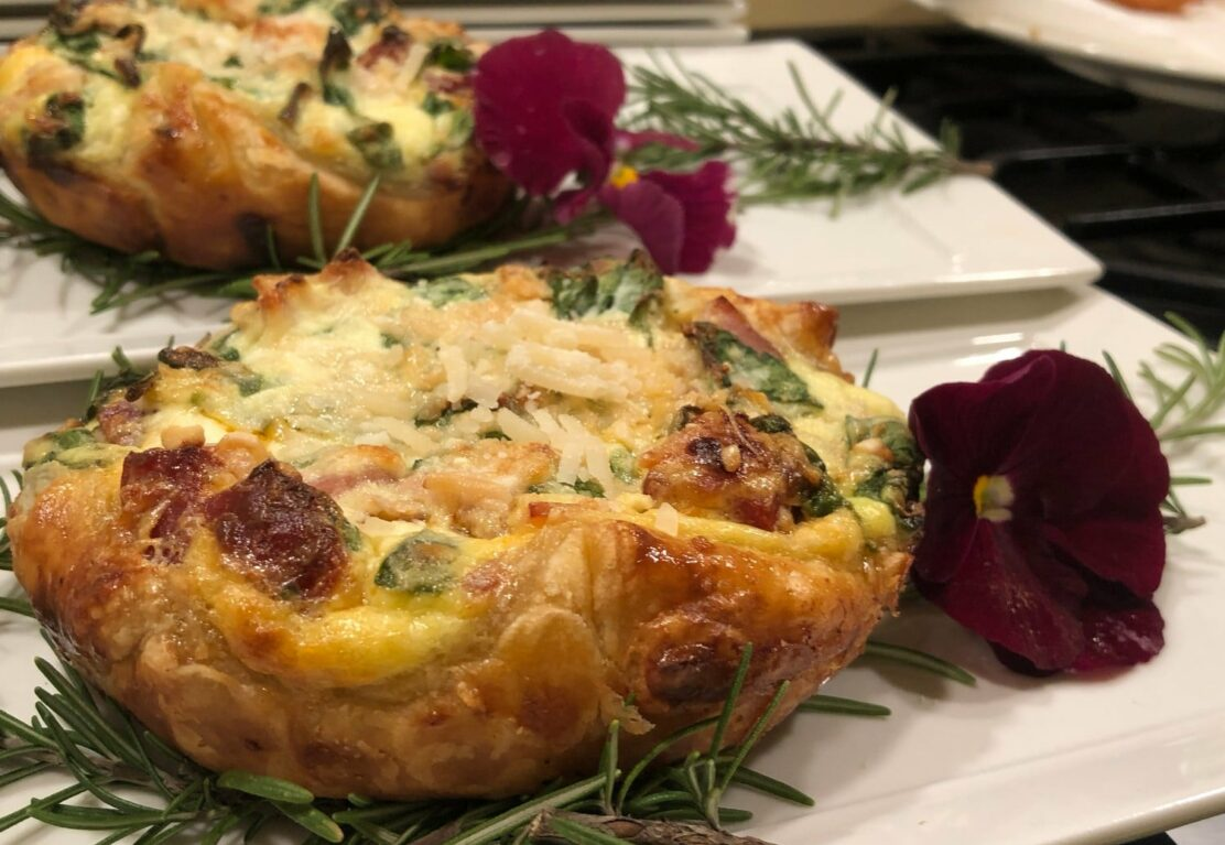 pastry with meat with rosemary and purple flower garnish on white dish at Stonehurst Place