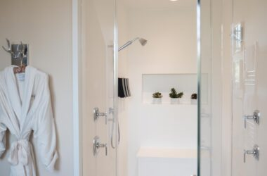 Master Suite glass walk-in shower with white robe hanging on wall in Stonehurst Place