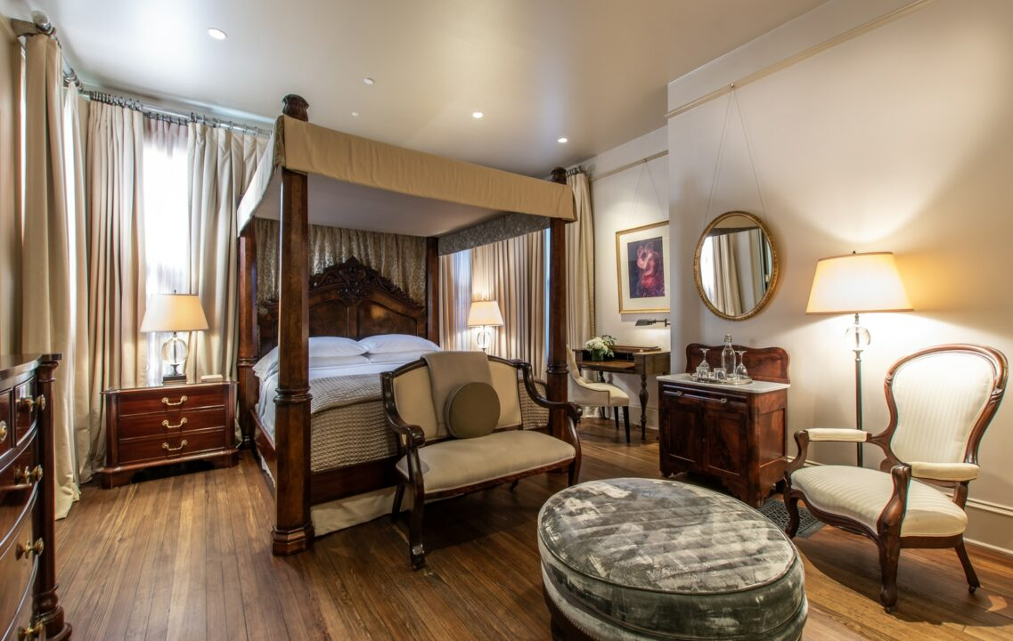 Hinman Suite with canopy bed and a sitting area with a velvet ottoman